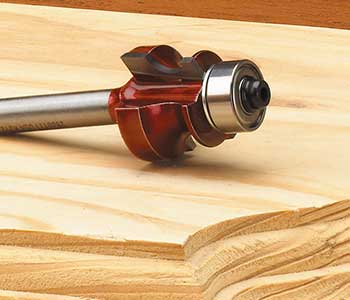 Router bit on top of shaped piece of wood